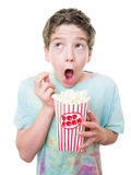 Kid at the movies. A young teen boy's expression at the movies while eating popcorn Stock Images