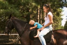 Kid with mum drive on horse top Royalty Free Stock Photos