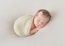 Kid napping wrapped, arm hanging out. Adorable kid napping wrapped with a scarf, arm hanging out of it, sleeping tight Royalty Free Stock Photos