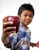Kid offering apple. Young boy showing apple Stock Photo