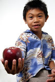 Kid offering apple Stock Photography