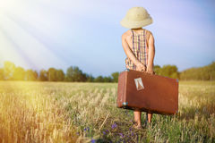 Kid with old suitcase walking away on sunny flare Royalty Free Stock Image