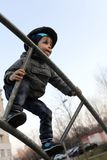 Kid overcomes obstacles. At outdoor playground in spring Royalty Free Stock Photo
