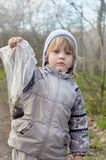Kid with packet of ground. Portrait of little boy holding cellophane packet with ground, authentic shot Royalty Free Stock Images