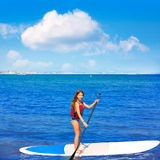 Kid paddle surf surfer girl with row in the beach Royalty Free Stock Photos
