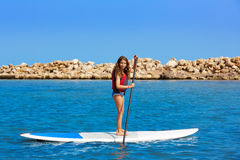 Kid paddle surf surfer girl with row in the beach Stock Images