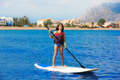 Kid paddle surf surfer girl with row in the beach Royalty Free Stock Photo