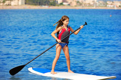 Kid paddle surf surfer girl with row in the beach. Kid paddle surf surfer girl with row in mediterranean beach stock photography