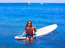 Kid paddle surf surfer girl with row in the beach Stock Image