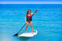 Kid paddle surf surfer girl with row in the beach Royalty Free Stock Images