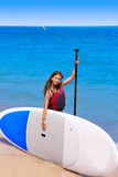 Kid paddle surf surfer girl with row in the beach Stock Photos