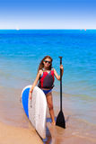 Kid paddle surf surfer girl with row in the beach Royalty Free Stock Photography