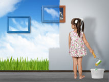 Kid with paint brush painting wall in color of nature Stock Photos