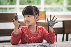 Kid with painted hand in art classroom. Kid with dirty painted hand in art classroom stock images