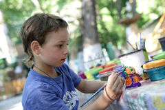 Kid painting clay figure Royalty Free Stock Photo