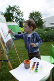 Kid painting at easel Stock Images