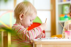Kid painting at home or nursery Stock Photo