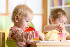 Kid painting with paintbrush Stock Photo