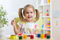 Kid painting with paintbrush Royalty Free Stock Photo