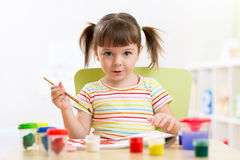 Kid painting with paintbrush Stock Images