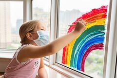 Kid painting rainbow during Covid-19 quarantine at home. Girl near window. Stay at home Social media campaign for coronavirus