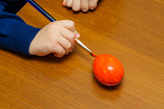 Kid painting red easter egg Stock Photos