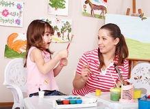 Kid painting with teacher in classroom. Royalty Free Stock Photography