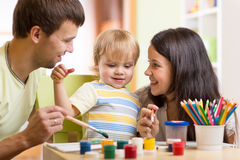 Kid painting together with parents ay home Royalty Free Stock Photo