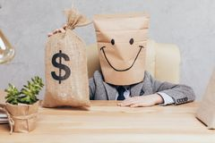 Kid with paper bag on head holding money bag while sitting at workplace. Isolated on grey stock photography