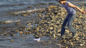 Kid with paper boat into water at beach. Little boy child puts paper ship on sea surface. ship sailing. Dreams, future. Childhood, summer, freedom, little stock video footage