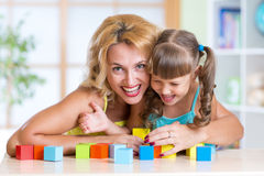Kid and parent playing in the room. Happy Kid and Parent Playing block Toys in playroom at nursery Royalty Free Stock Image