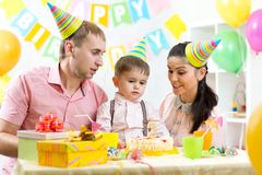Kid with parents blow candle on birthday cake Royalty Free Stock Photo
