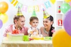 Kid with parents blow candles on birthday cake Royalty Free Stock Image