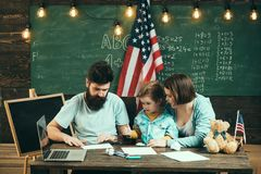 Kid with parents in classroom with usa flag, chalkboard on background. American family sit at desk with son and usa flag. Parents teaching son american stock photography