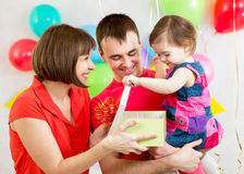 Kid with parents opening gift box Royalty Free Stock Images