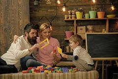 Kid with parents play with plastic blocks, build construction. Family on busy face spend time together in playroom. Father, mother and cute son play with stock image