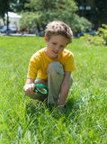 Kid in the park looking the grass with a magnifying glass. Cute boy doing experiments outdoors. Royalty Free Stock Image