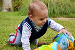Kid in the park playing with a ball. Adorable boy playing with a ball in the garden royalty free stock photo