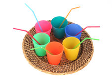 Kid party cups with straws. Cups of different colors on a beautiful tray isolated on white background Stock Photography