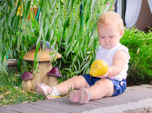 Kid with a pear. Little baby sitting in a park under a tree with a pear in her hands stock images