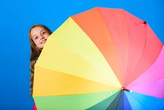 Kid peek out colorful rainbow umbrella. Color your life. Girl cheerful hide behind umbrella. Colorful umbrella accessory royalty free stock photography