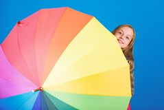 Kid peek out colorful rainbow umbrella. Color your life. Girl cheerful hide behind umbrella. Colorful umbrella accessory. Weather forecast concept. Stay royalty free stock photos