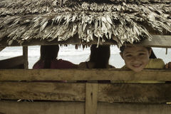 Kid peeping from bamboo hut. Photo of cute asian kid peeping from a bamboo hut at the beach stock image