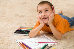 Kid with pencils on the carpet. Stock Photography