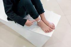 Kid& x27; pies de s con la herida y el vendaje del rasguño Fotos de archivo libres de regalías