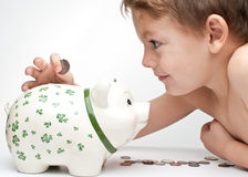 Kid with a piggy bank. Young child , boy saves change in his piggy bank Stock Image