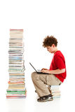Kid and pile of books. Young boy sitting next to pile of books on white background Stock Images
