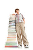 Kid and pile of books. Young boy standing next to pile of books on white background Stock Image