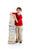 Kid and pile of books. Young boy standing next to pile of books on white background Stock Images