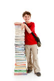 Kid and pile of books. Young boy standing next to pile of books on white background Royalty Free Stock Images